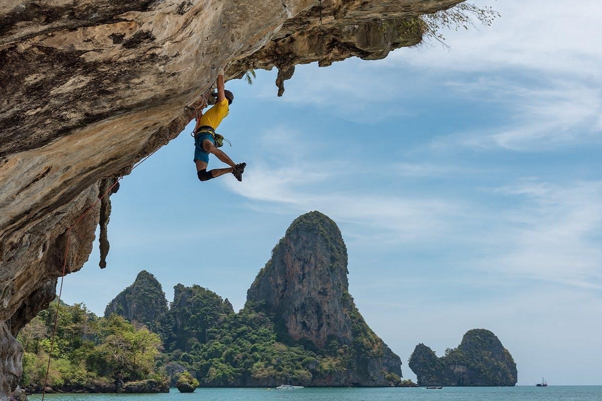 A rock climber hangs from a clifff.