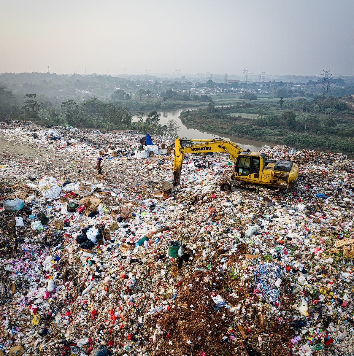 An excavator moving waste at a landfill site.  Let's keep clothing out of landfill by choosing to repair, reuse, recycle our garments.