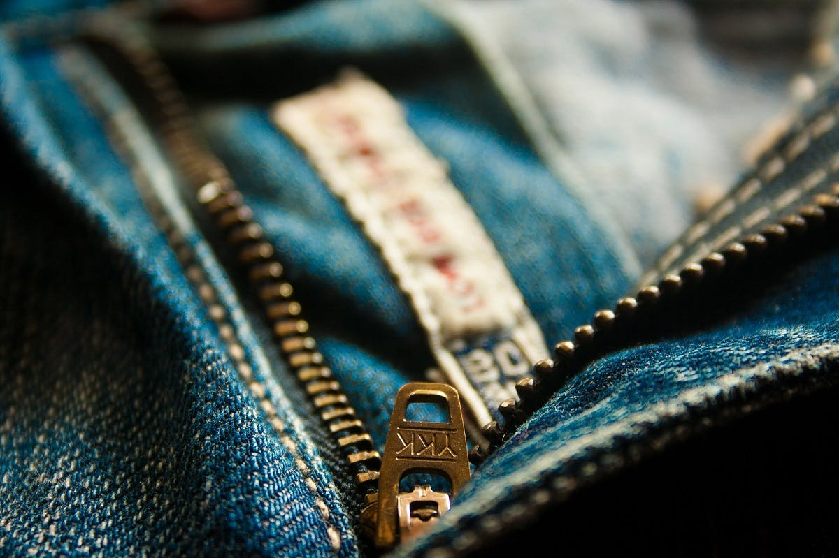 A close up photo of a YKK zip on a pair of blue jeans. Look for these signs of quality when trying to avoid fast fashion.