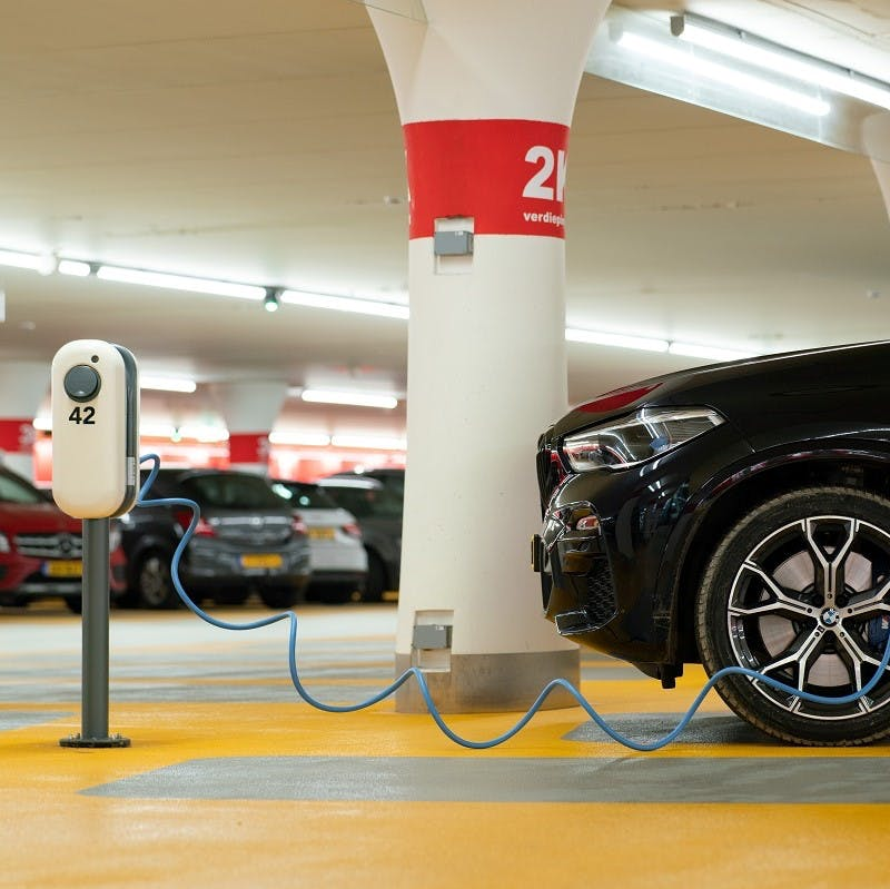 An electric company car being charged at work in an underground carpark.
