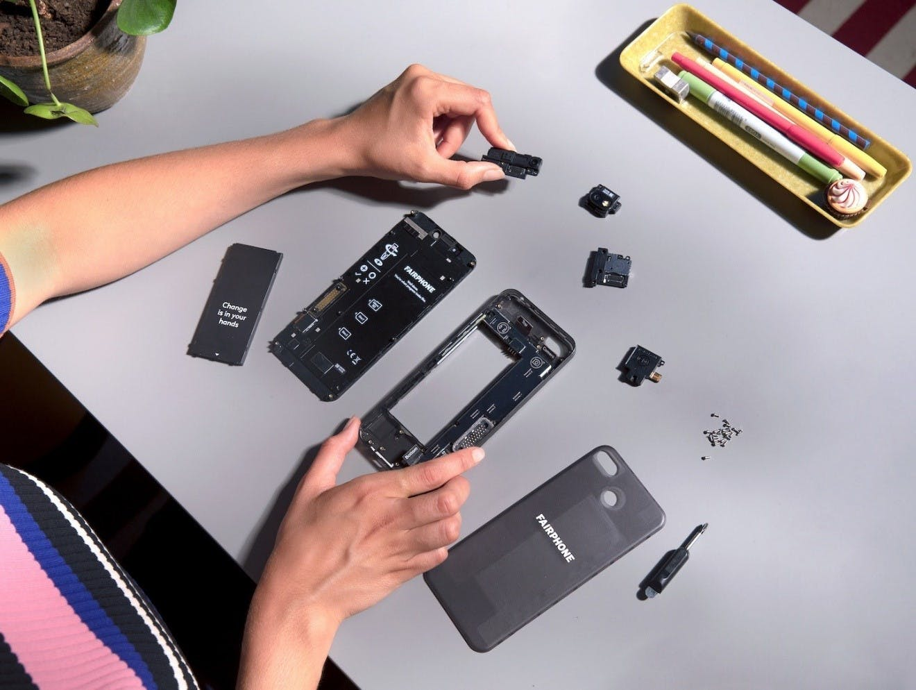 A person dismantling their sustainable and ethical smartphone by Fairphone.