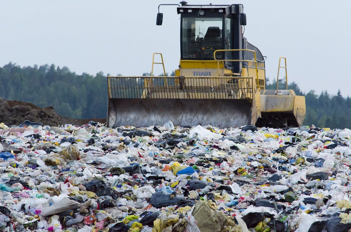 A bulldozer surrounded by waste at al landfill site adjacent to a beautiful forest