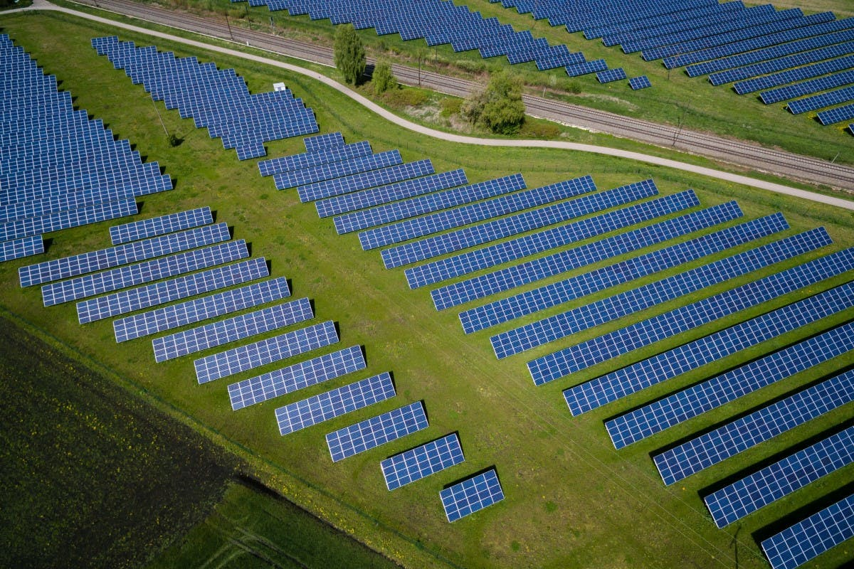 Aerial photo of a solar farm with solar panels layed out over green grass.