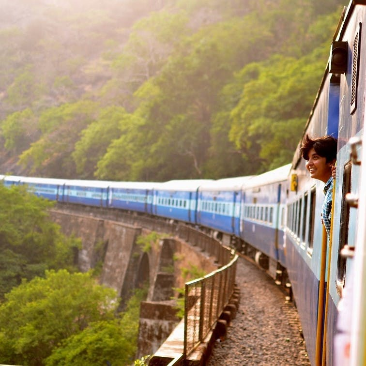 A lady pokes her head out of a train window to enjoy the view, as the train passes over a bridge. Travelling by train is a relaxing  and low emissions solution to travelling without without flying