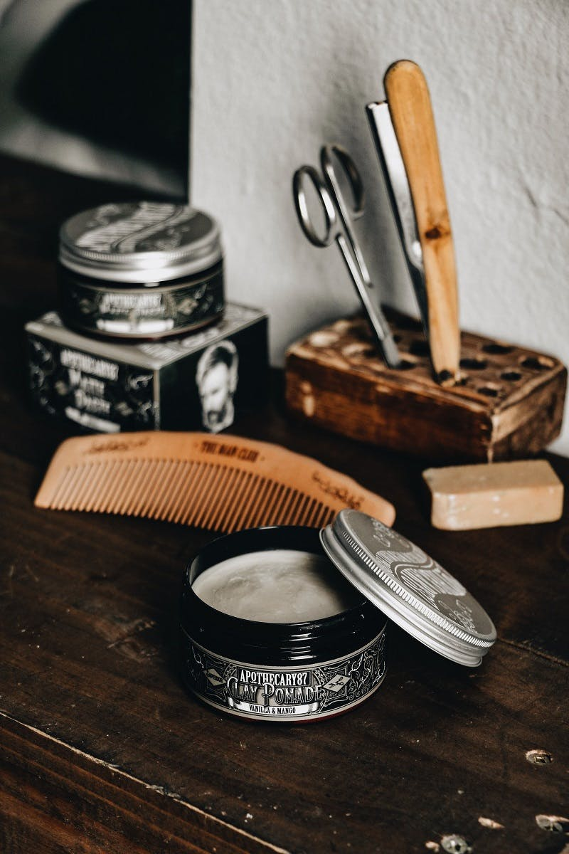 A cut throat razer, barber's scissors and solid bar of shaving balm on a shelf at a barber's shop.