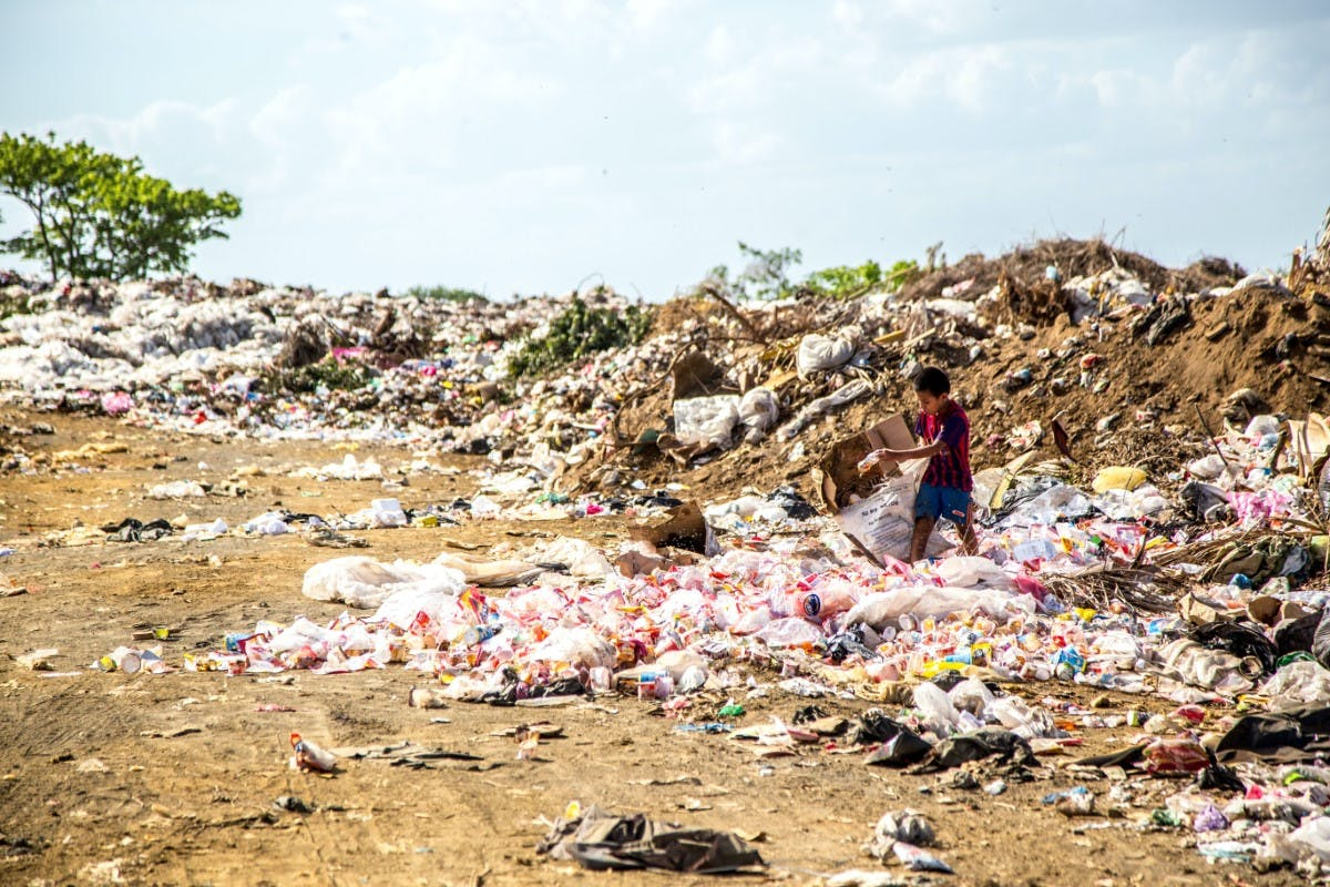 Child walking through landfill