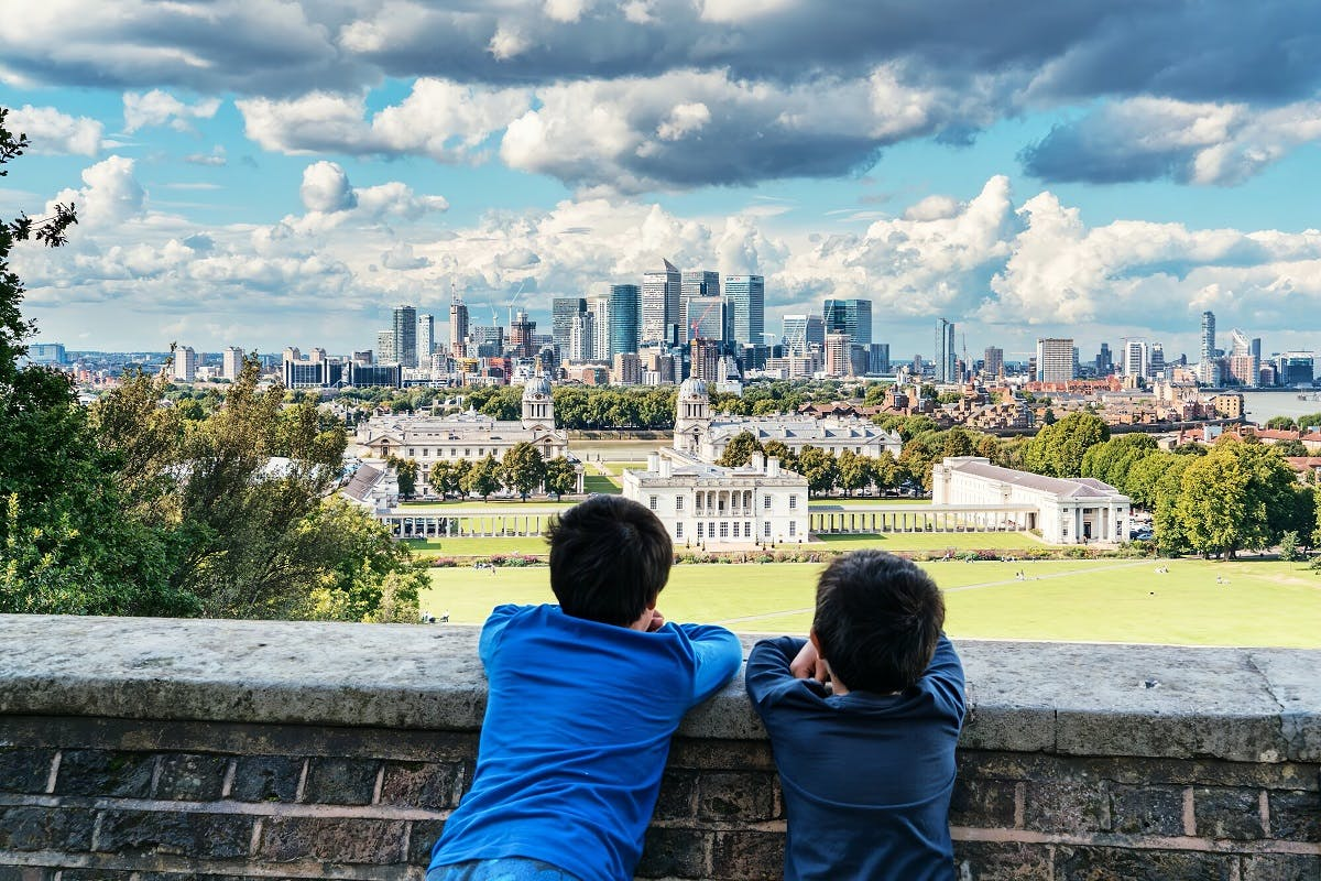 Two boys look over a wall towards the city of London.