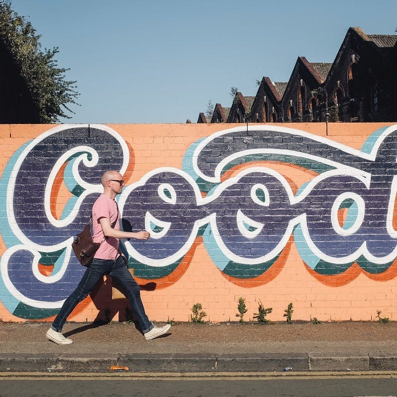 "A man walking to work, past a wall with bright blue and orange graffiti reading ""good""."