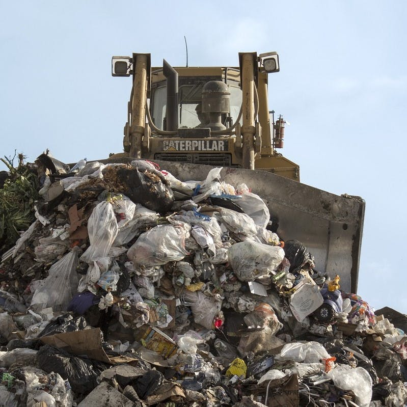 A digger pushing huge piles of waste across a toxic landfill site. Let's reduce, reuse, recycle our clothing to keep it out of landfill.