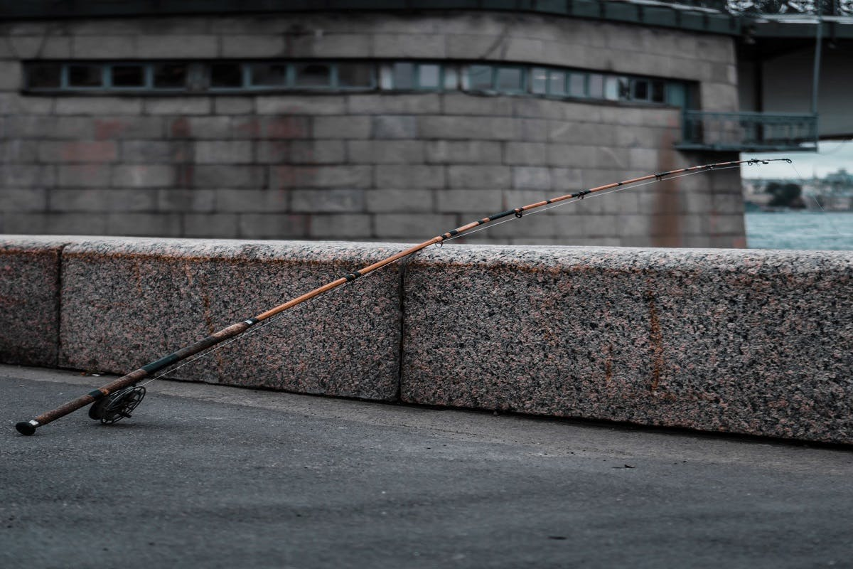 An unattended fishing rod rests against a wall of a waterway.