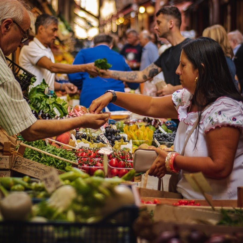 People shopping for fruit and vegetables at a busy market. Do you consciously think how to reduce food waste when you are food shopping?
