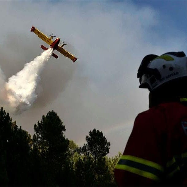 A plane drops water over a forest fire in Portugal.