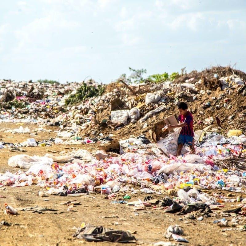 Child walking through landfill