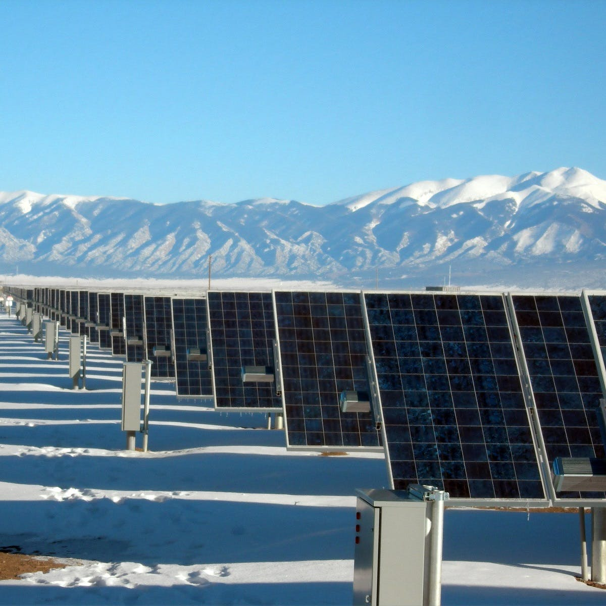 A row of solar panels under blue skies  in front of snow capped mountains