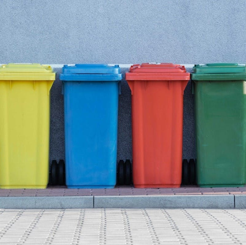 Four colorful recycling bins side by side on a sidewalk.