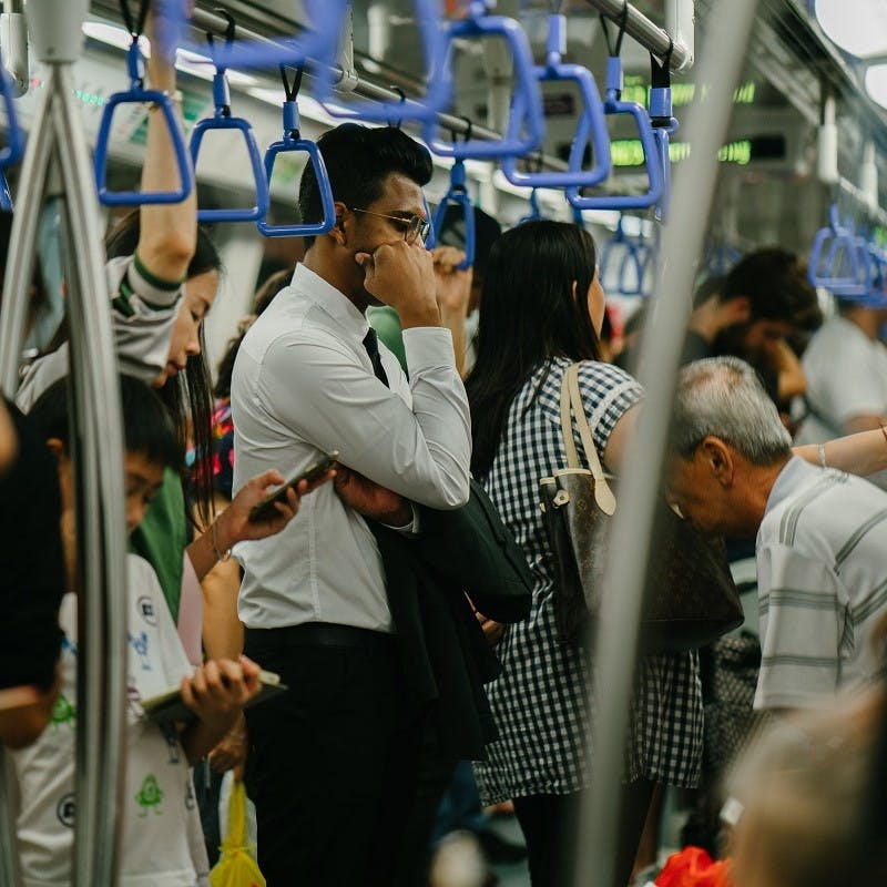 Passengers taking advantage of their commute by reading or listening to podcasts. Public transport is the stalwart of the green commute.