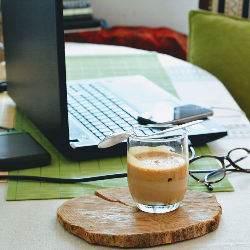A work from home office complete with laptop, mobile, glasses and a fresh coffee. Instead of a green commute, eliminate the commute by working from home.