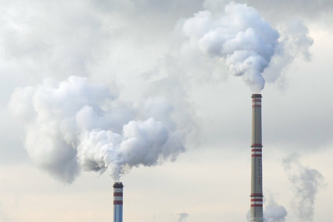 Two factory chimneys pumping CO2 into the atmosphere. An imbalance of CO2 in the atmosphere causes climate change