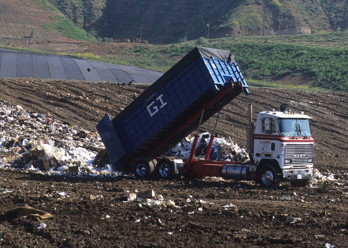 A truck dumping waste at a landfill site