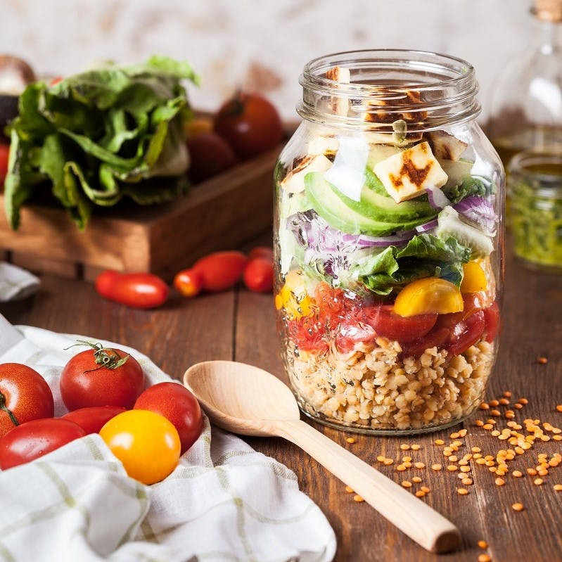 A jar filled with a variety of colourful foods. getting creative in the kitchen is one of many ways of how to reduce food waste at home.