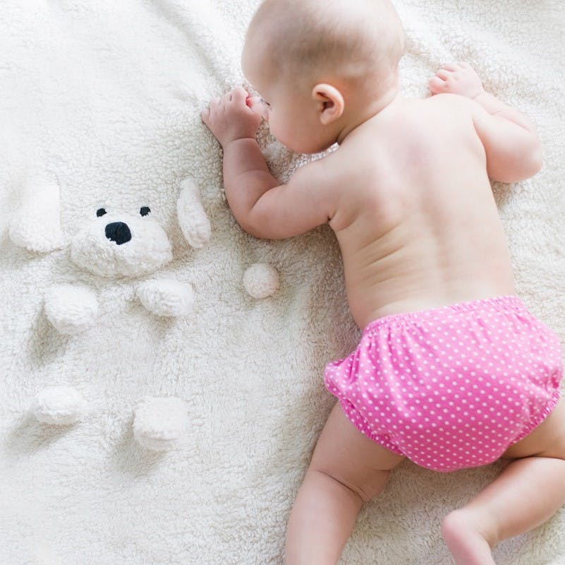 A baby dressed in a pink reusable cotton nappy next to its teddy bear.