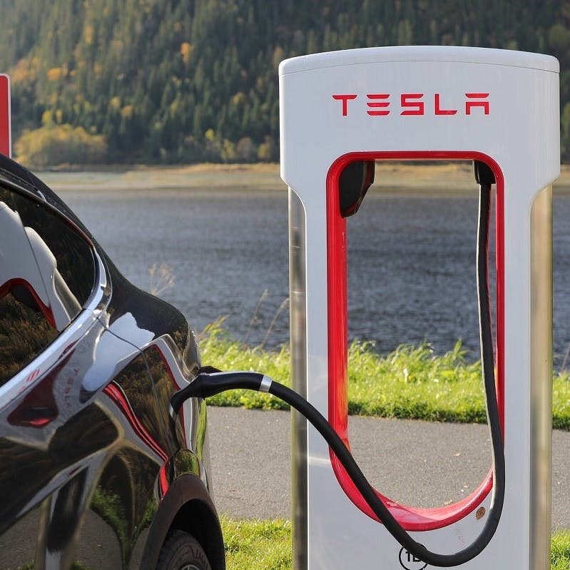 An electric Tesla car charging. With no exhaust system they have zero emissions and so a green commute option.