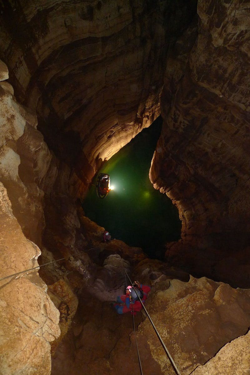 Cavers explore a cave with head torches and submerged in water up to waist-height
