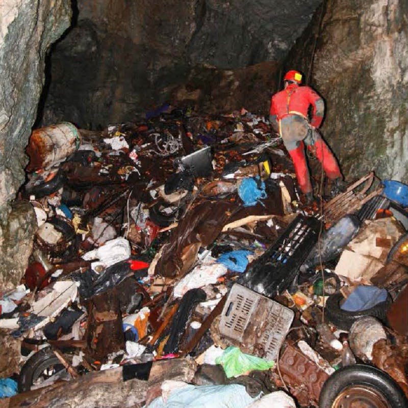 A caver in a full red suit and helmet abseils over a huge pile of solid waste inside Rupečica cave. Photo credit: PROTEUS project team.
