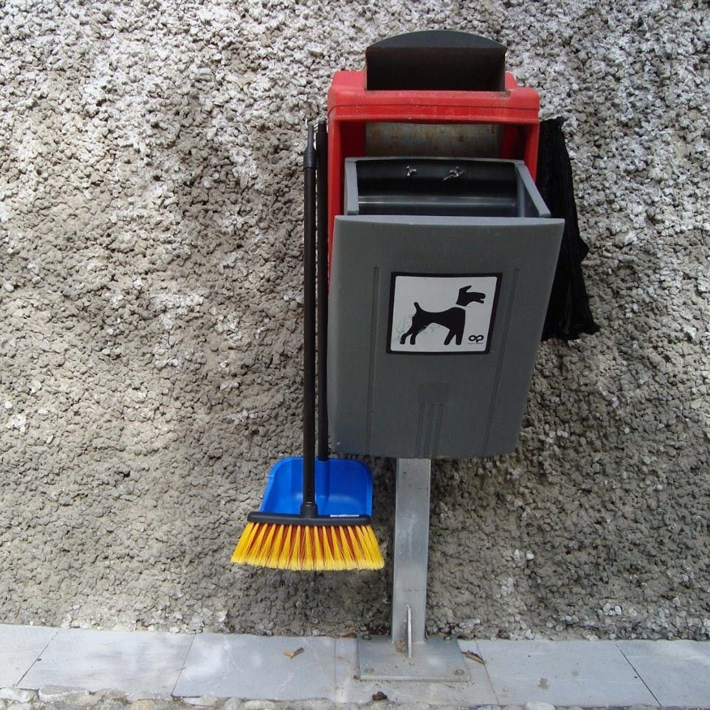 A dog poo bin complete with bags, a dust pan and brush.
