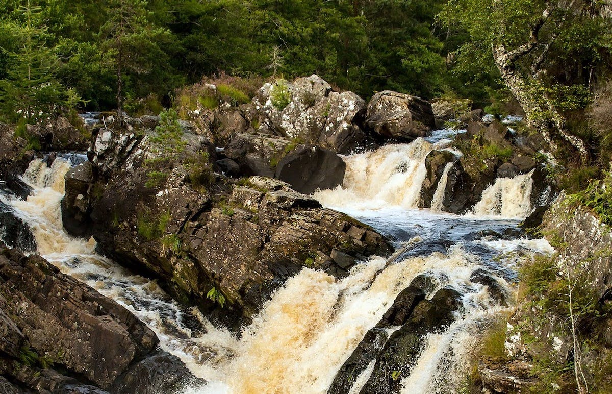 Water flows along a wooded river in Scotland