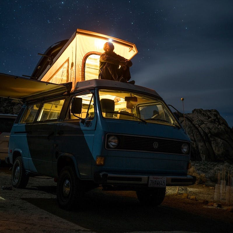 A man enjoying the nights sky from the roof of his remotely parked camper van.