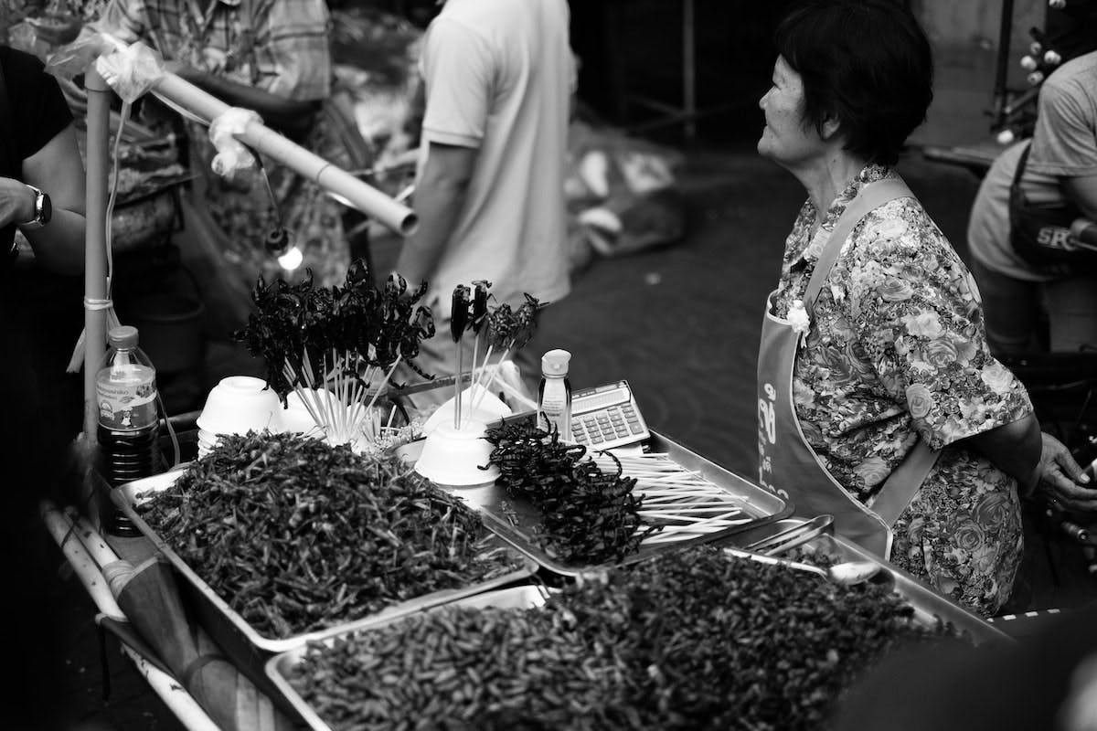 A black and white image of an edible insect market in Asia.