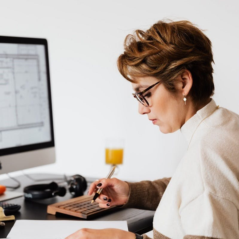 A lady reading online about home insulation hacks.