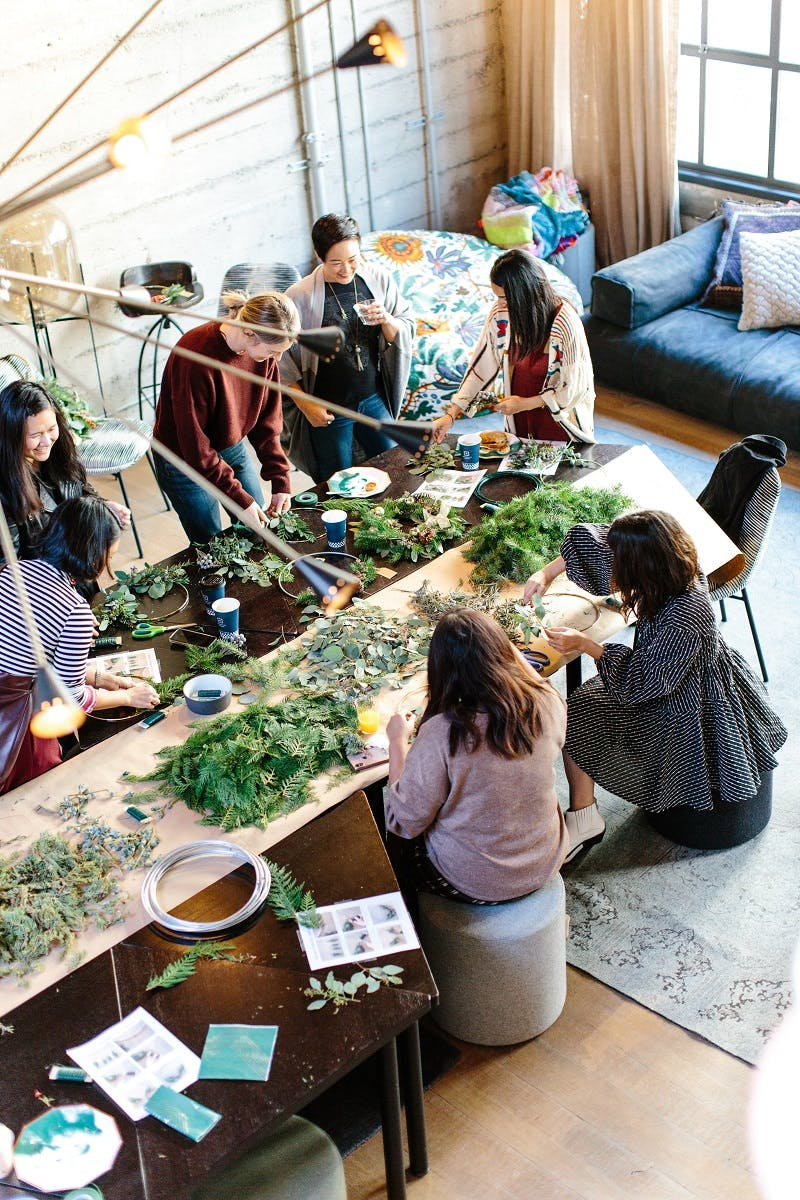 A group of friends gathered round a dining table with an assortment of leaves spread across the table.
