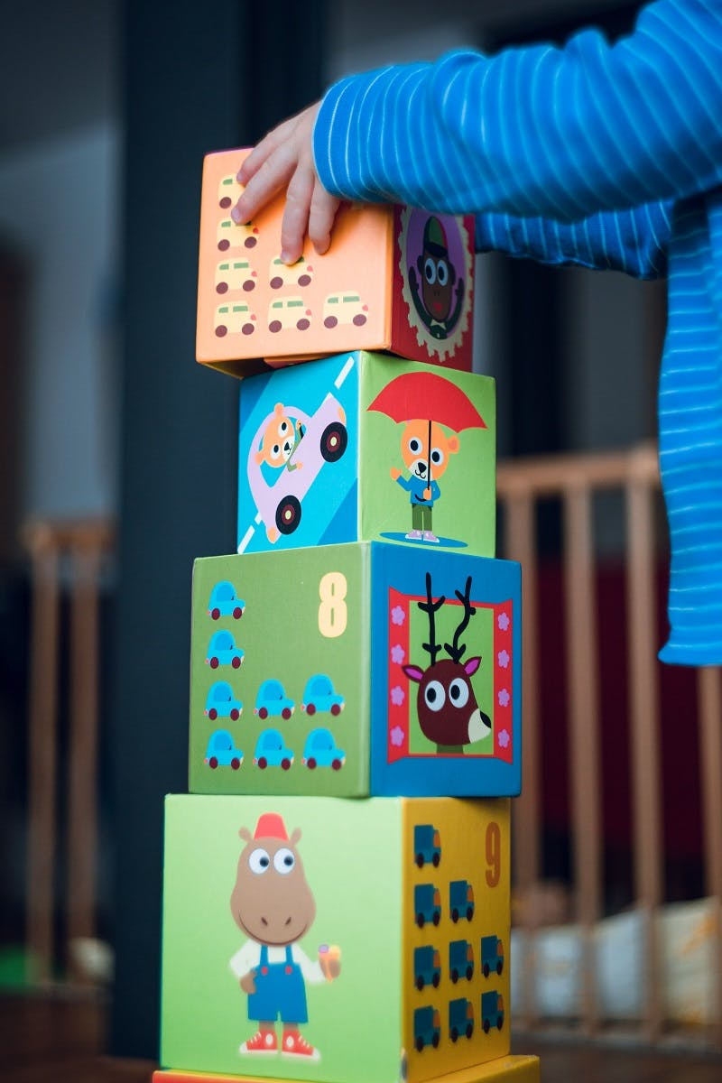 A toddler playing with toy blocks. A toy subscription is one of many ways to source eco friendly baby products.