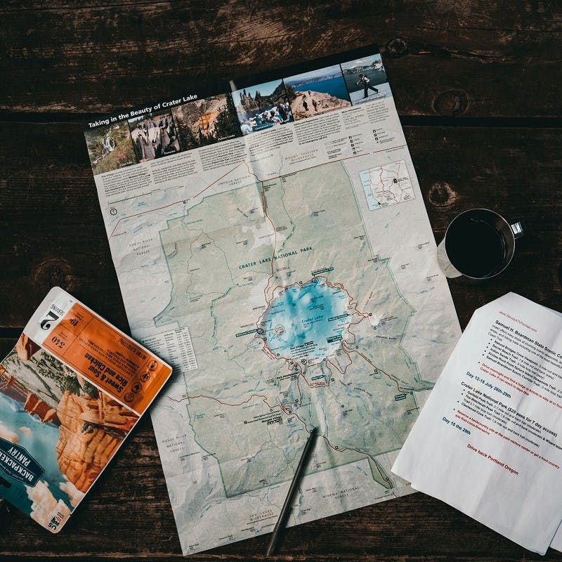 A map, a pen, a set of notes and a cup of coffee set out on a table as someone plans a travel without flying trip.