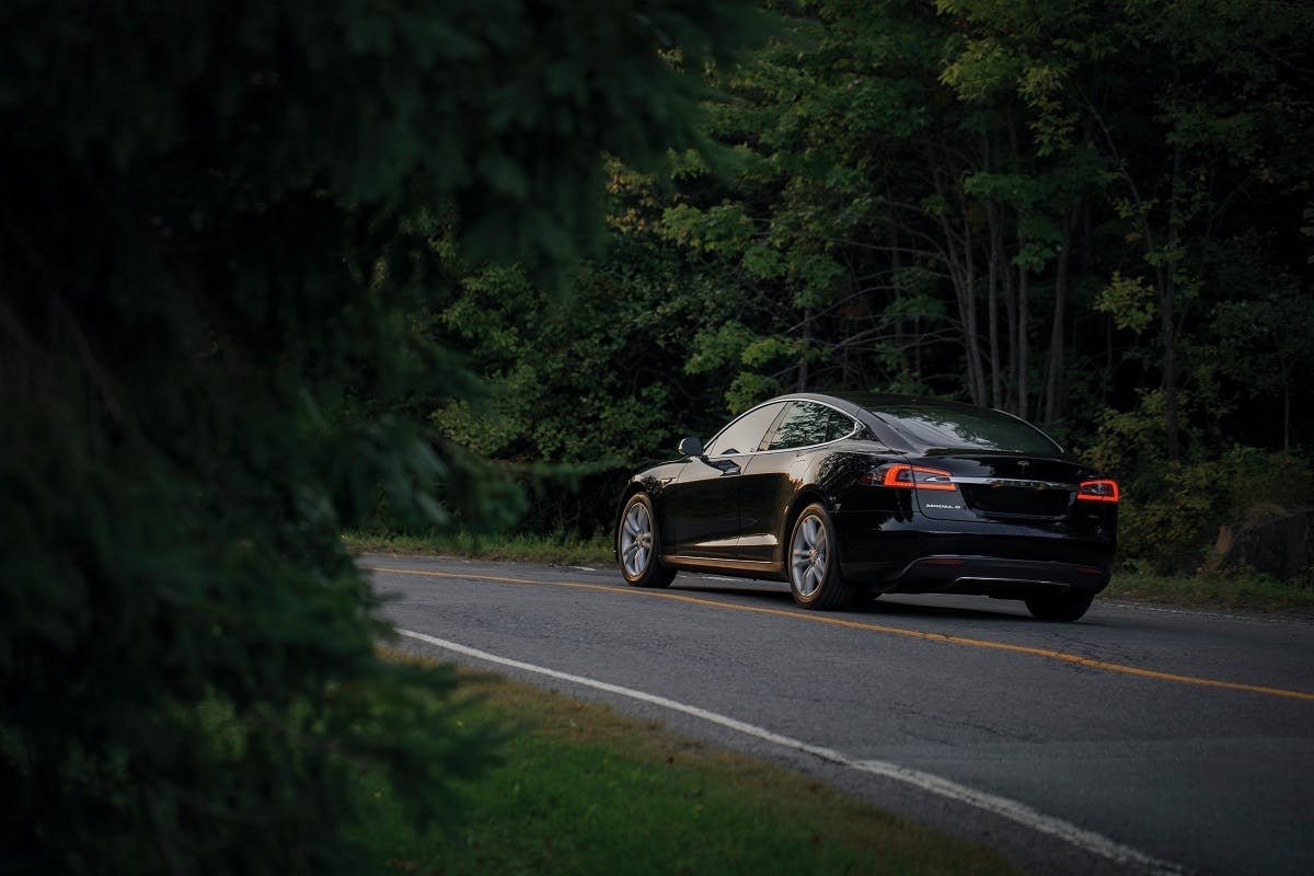 An electric car silently driving down a country lane.  Level of engine noise vs pedestrian safety is often talked about when discussing electric cars pros and cons.