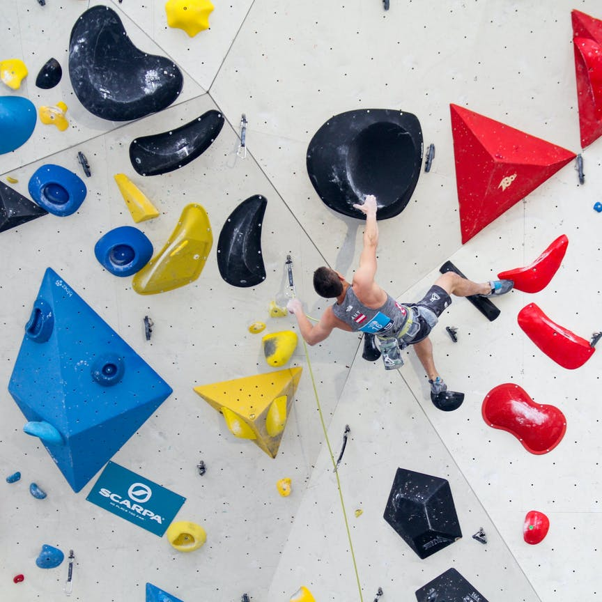 Climber lead climbing on an indoor climbing gym with colourful holds.