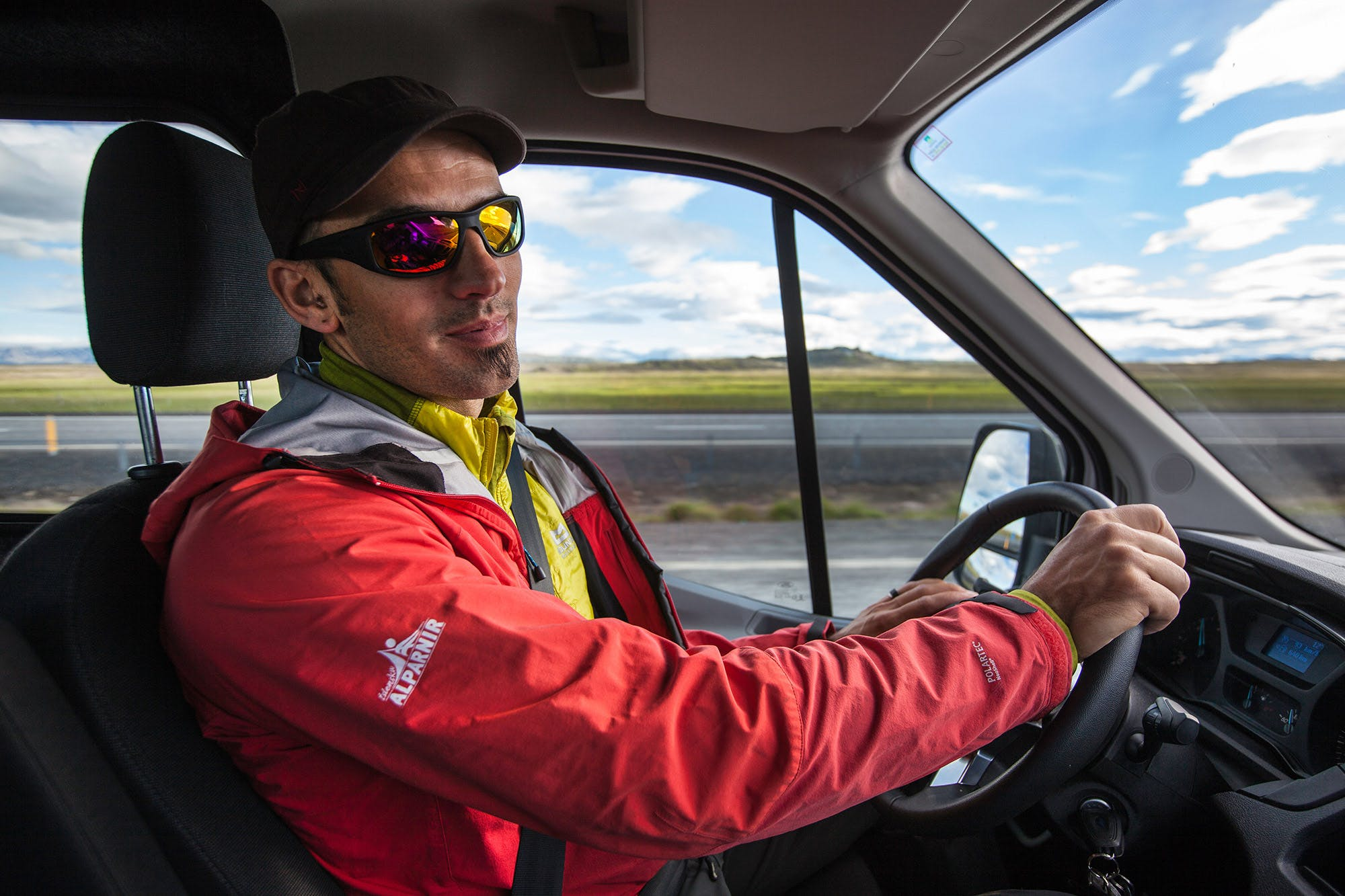 A guide driving a minibus on a day tour with Icelandic Mountain Guides