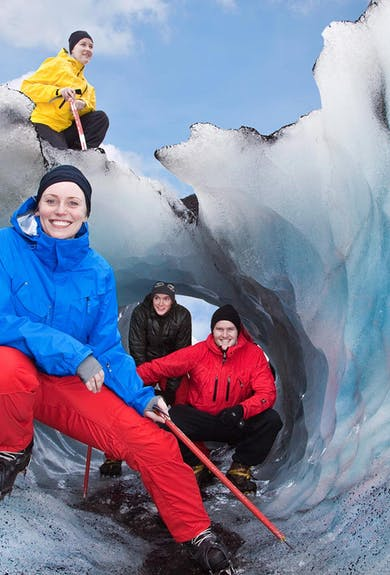 Smiling girl in front of more people around a ice tunnel on a glacier in Iceland