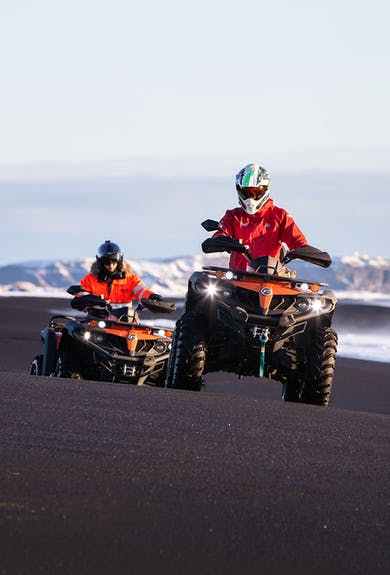 Two men dressed in red on an ATV tour on a black beach in Iceland