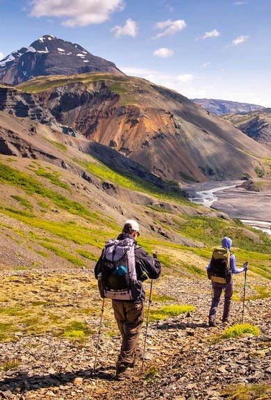 People hiking the beautiful Lonsoreafi area in Iceland with colorful mountains in the background