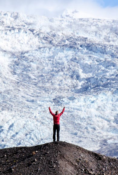 happy man in red looking at Svinafellsjokull standing on a hill (Sívafellsjökull)