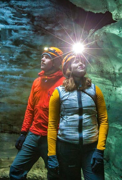 A couple standing in an ice cave in Iceland, wearing helmets with headlamps and gazing upwards
