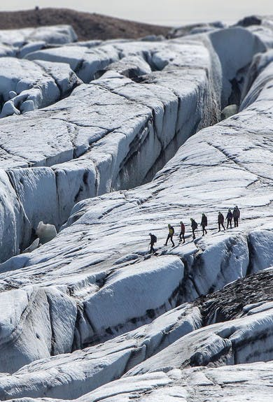 people hiking on Svinafellsjokull in glacier walk on a sunny day