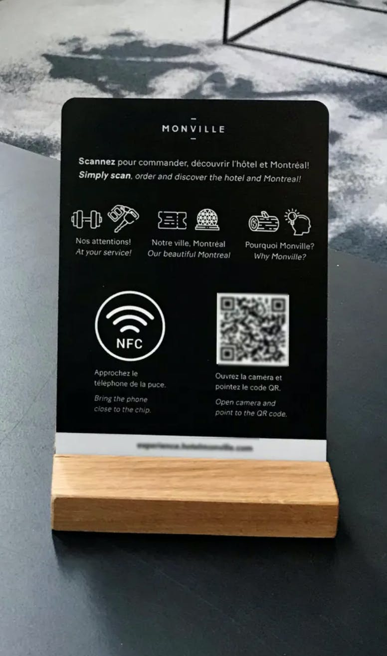 A poster of the Hotel Monville inviting to scan the QR code and the NFC chip