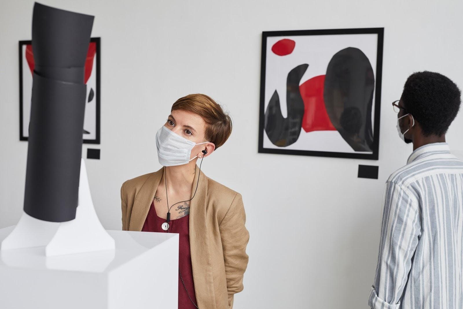 Femme portant un masque dans un musée.