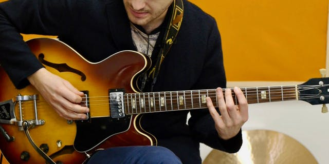 A Man Playing the Blues Scale on Guitar