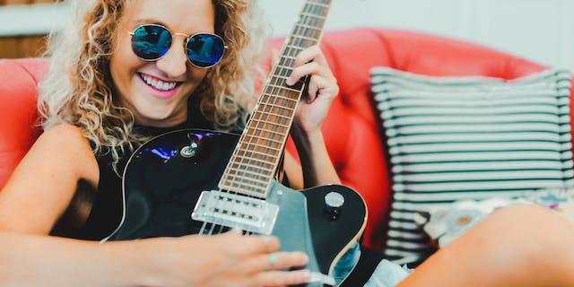 Trendy girl playing guitar
