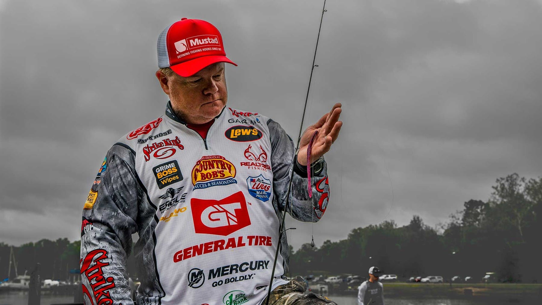 Portrait photo of American pro staffer Mark Rose holding up a rod rigged with a soft plastic bait.